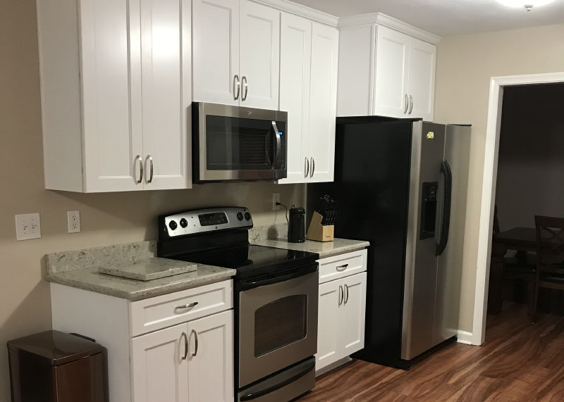 A renovated kitchen with hardwood floors and stainless steel appliances.