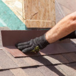 Roofer builder worker installing shingles on a new wooden roof with skylight