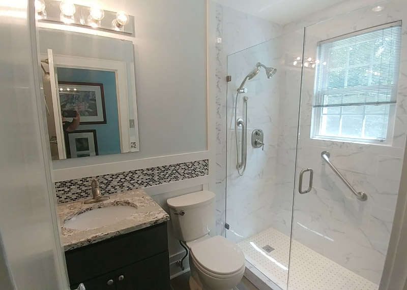 A remodeled bathroom with granite countertop, glass and tile shower